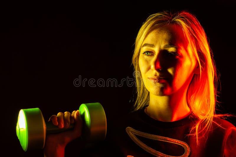 Una muchacha rubia hermosa joven en una camiseta negra est? llevando a cabo una pesa de gimnasia pl?stica verde en su mano que au foto de archivo libre de regalías