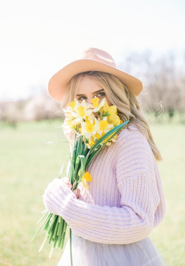 Una muchacha rubia hermosa joven en un sombrero y una falda larga enorme con los ramos de narcisos en la primavera cultivan un hu fotos de archivo libres de regalías