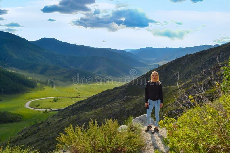 Una muchacha rubia hermosa joven se coloca al borde de un acantilado en t fotografía de archivo