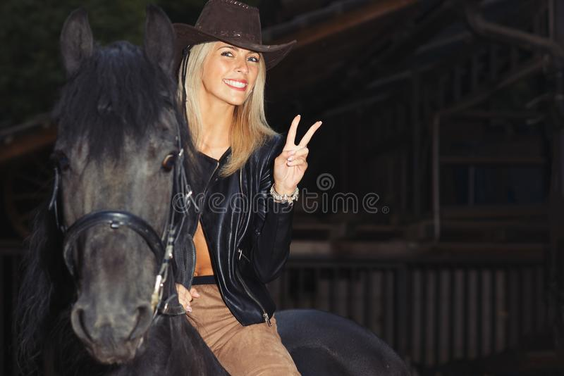 Una muchacha rubia hermosa sobre un caballo negro imagenes de archivo