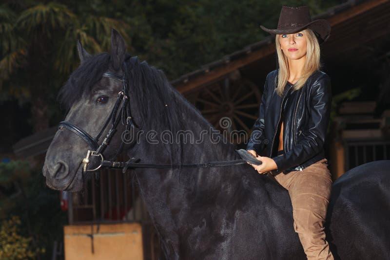 Una muchacha rubia hermosa sobre un caballo negro imágenes de archivo libres de regalías