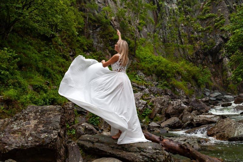 Una muchacha rubia joven en una actitud elegante levanta un gabinete de señora se viste para arriba en las montañas contra una ca foto de archivo