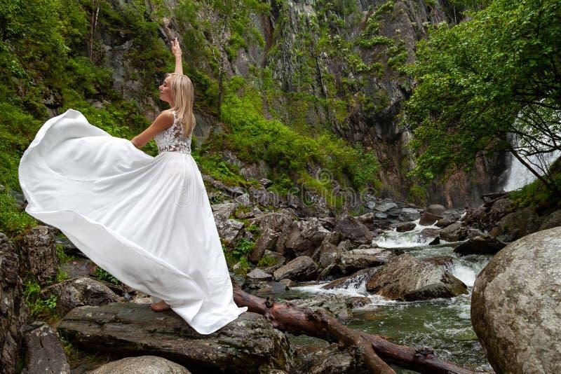 Una muchacha rubia joven en una actitud elegante levanta un gabinete de señora se viste para arriba en las montañas contra una ca fotos de archivo