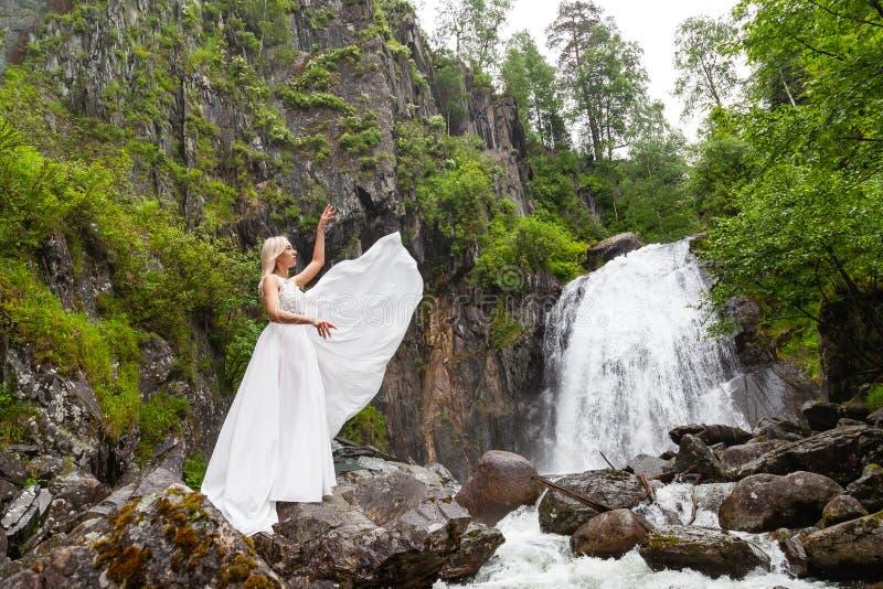 Una muchacha rubia joven en una actitud elegante levanta un vestido del gabinete de señora en las montañas contra una cascada y l foto de archivo