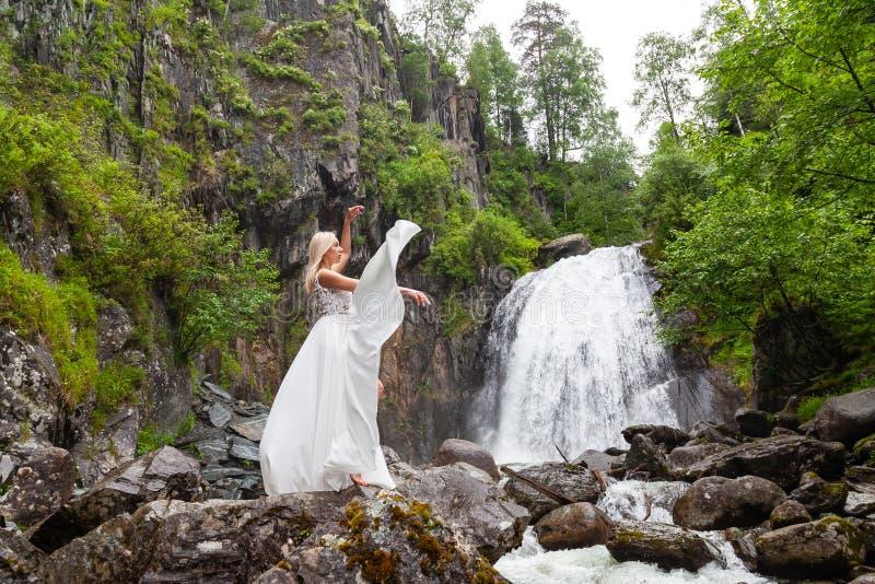Una muchacha rubia joven en una actitud elegante levanta un vestido del gabinete de señora en las montañas contra una cascada y l imagen de archivo