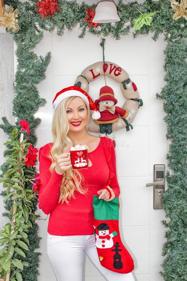 Una muchacha rubia joven hermosa en el casquillo de Papá Noel se coloca en la puerta principal adornada con una guirnalda y las r imágenes de archivo libres de regalías