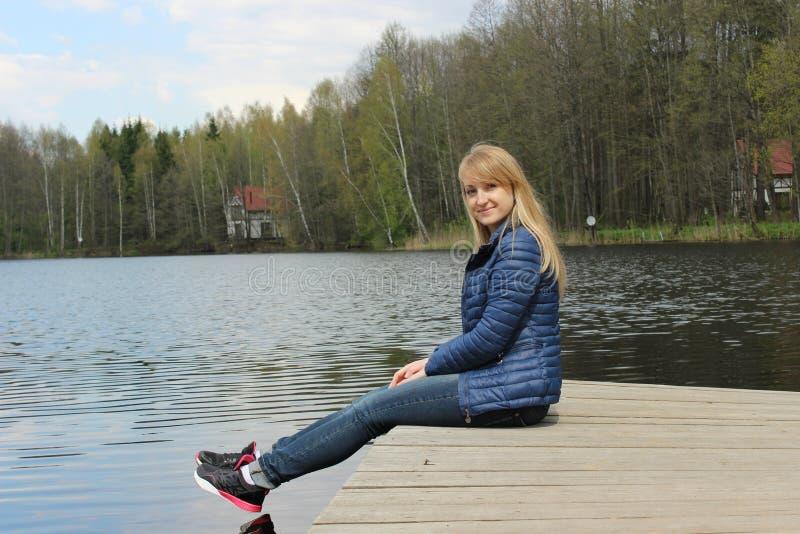 Una muchacha rubia joven se está sentando en la orilla del lago foto de archivo libre de regalías