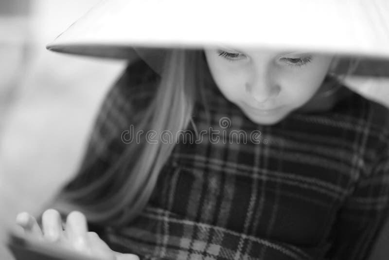 Una muchacha rubia linda en un sombrero de paja grande imagenes de archivo