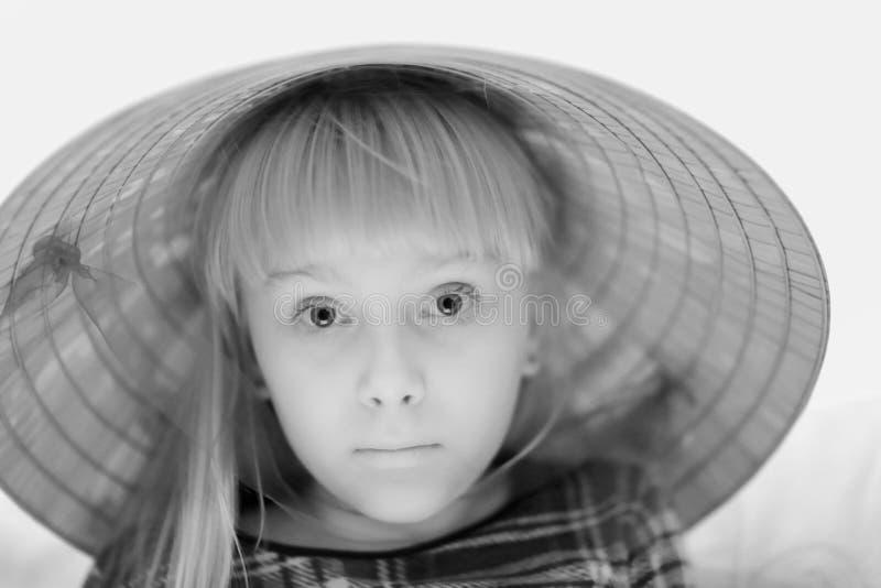 Una muchacha rubia linda en un sombrero de paja grande imagen de archivo libre de regalías