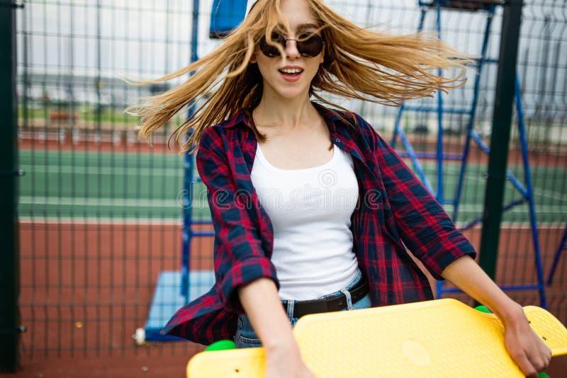 Una muchacha rubia sonriente bonita que lleva la camisa a cuadros, el casquillo blanco y las gafas de sol está caminando a través imagen de archivo