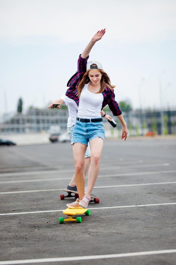 Una muchacha rubia sonriente hermosa que lleva la camisa a cuadros, el casquillo blanco y pantalones cortos del dril de algodón e imagen de archivo libre de regalías