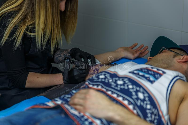 Una muchacha rubia tatúa exactamente el brazo de un muchacho en su estudio del tatuaje fotos de archivo