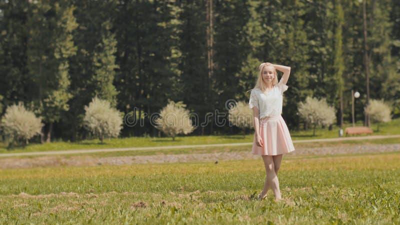 Una muchacha rusa joven feliz está corriendo en el parque de la ciudad fotografía de archivo libre de regalías