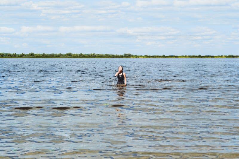 Una muchacha se baña en el río imagen de archivo