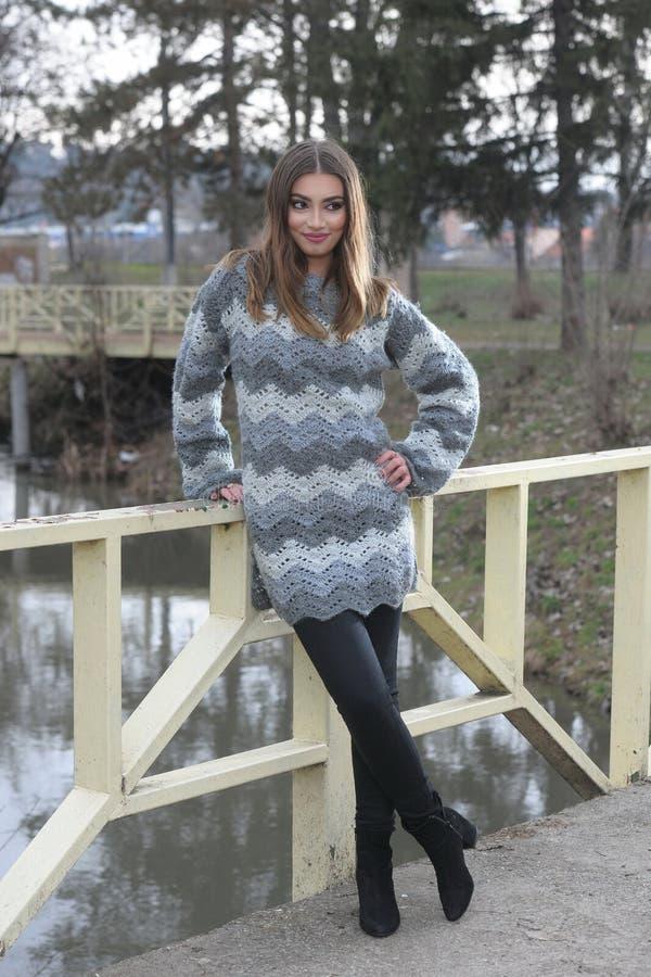 Una muchacha se coloca al lado de un puente, vestido en GR hecho punto fotos de archivo libres de regalías