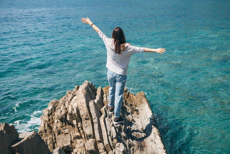Una muchacha se coloca en una orilla rocosa imágenes de archivo libres de regalías