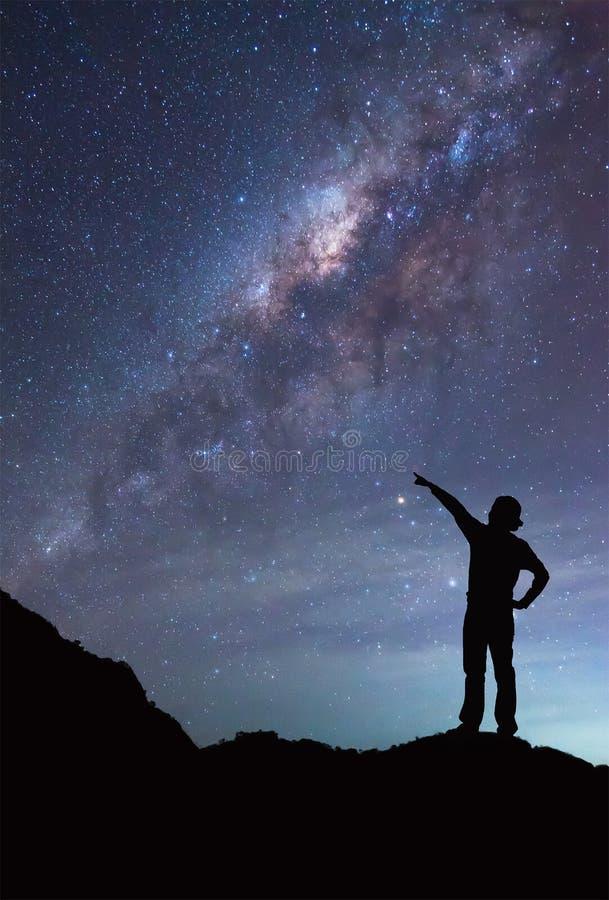 Una muchacha se está colocando al lado de la galaxia de la vía láctea que señala en una estrella brillante imagen de archivo
