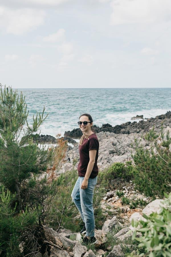 Una muchacha se está colocando en una costa de piedra fotografía de archivo libre de regalías