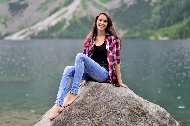 Una muchacha se está sentando en una roca grande contra la perspectiva de un la fotos de archivo libres de regalías