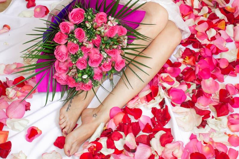 Una muchacha se sienta en una cama con un ramo rosado de flores Un regalo para el día de fiesta Pies femeninos imagenes de archivo