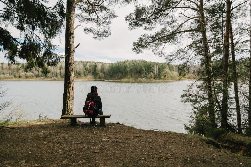 Una muchacha se sienta en el borde del acantilado en una silla y árboles fotografía de archivo