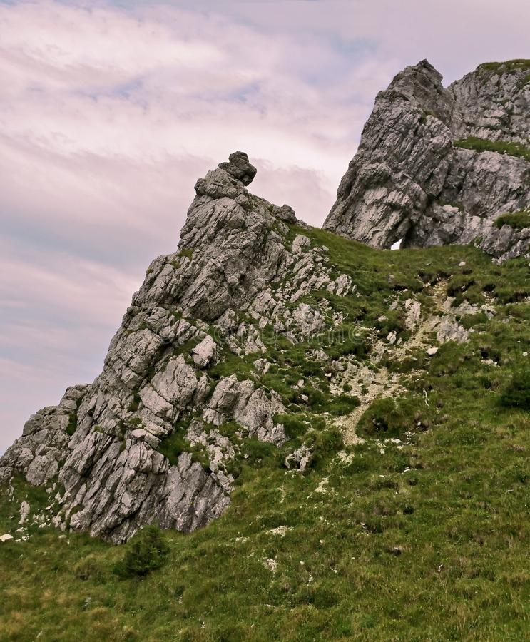 Una muchacha se sienta en la roca fotos de archivo
