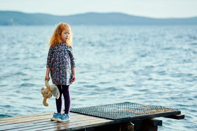 Una muchacha sola con un conejito de la felpa se está colocando en el embarcadero y el retrete imagen de archivo