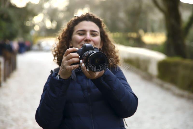 Una muchacha sonriente con el pelo rizado que sostiene una cámara en el parque en fondo del bokeh fotografía de archivo libre de regalías