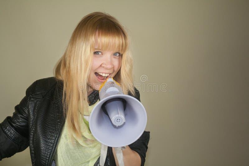 Una muchacha sonriente con un megáfono fotos de archivo