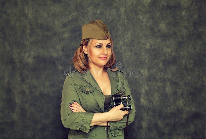 Una muchacha sonriente en casquillo de guarnición con los prismáticos militares desde la Segunda Guerra Mundial fotografía de archivo libre de regalías