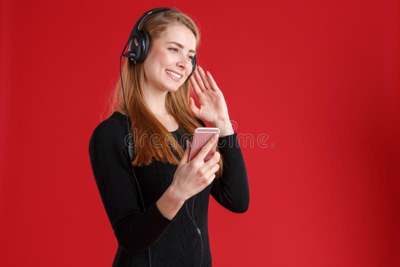 Una muchacha sonriente en un suéter negro, escuchando la música en auriculares y sosteniendo un smartphone en su mano foto de archivo
