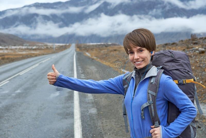 Una muchacha sonriente joven está viajando en las montañas para el coche en el camino que hace autostop, aumenta su mano imagen de archivo libre de regalías