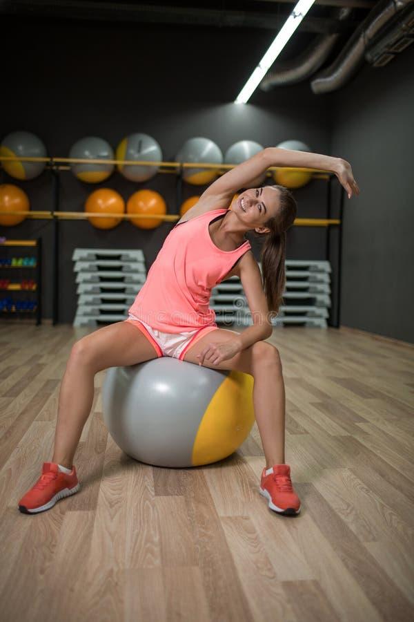 Una muchacha sonriente que hace ejercicios de la aptitud Se divierte a la mujer que estira en una bola del ajuste en un fondo del foto de archivo
