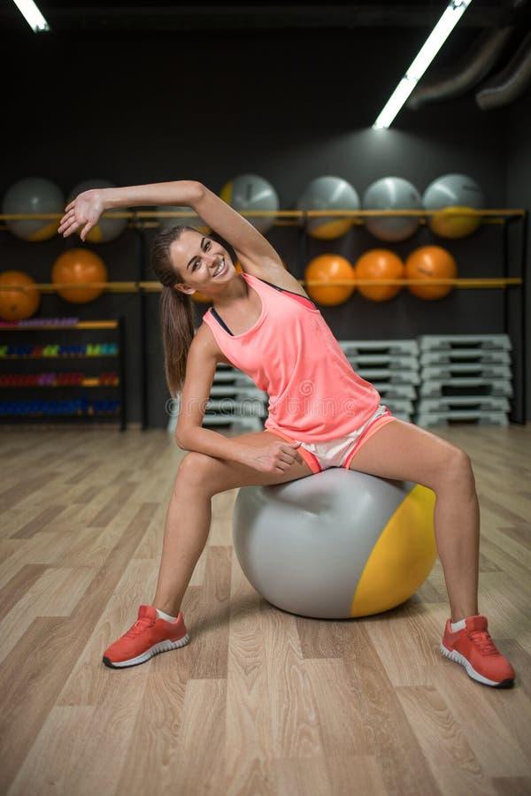 Una muchacha sonriente que hace ejercicios de la aptitud Se divierte a la mujer que estira en una bola del ajuste en un fondo del imagen de archivo