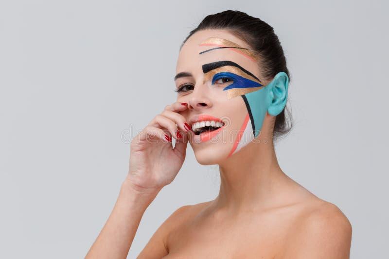 Una muchacha sonriente, que tiene un maquillaje creativo del color, lleva a cabo la mano para hacer frente imagen de archivo libre de regalías