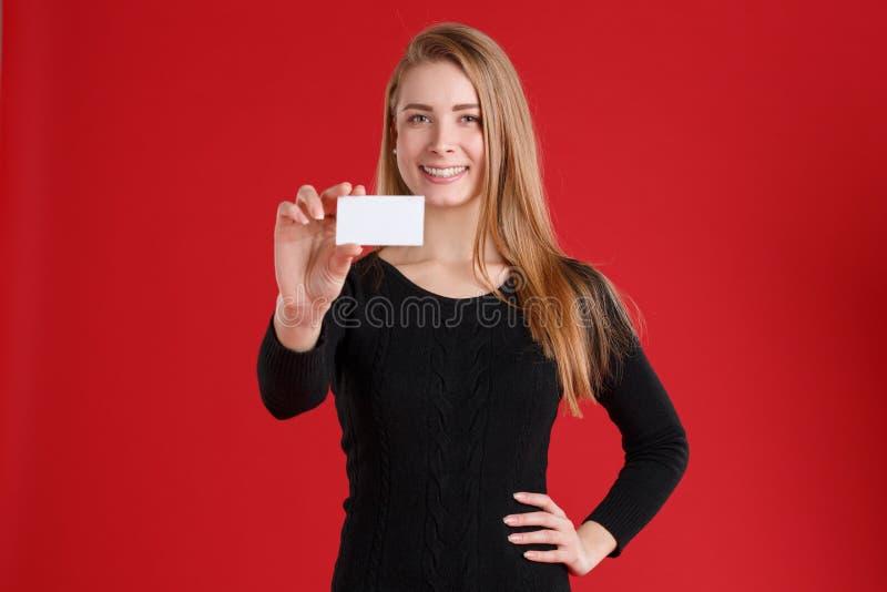 Una muchacha, sosteniendo una tarjeta de visita y un tablero blanco con los papeles, y una sonrisa linda fotografía de archivo