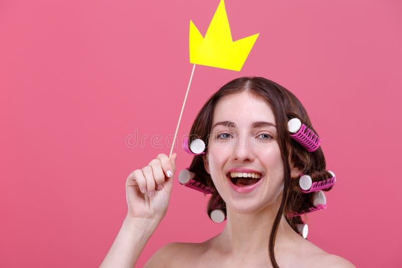 Una muchacha sostiene una corona de papel amarilla sobre su cabeza en un palillo y sonríe lindo En un fondo rosado imágenes de archivo libres de regalías
