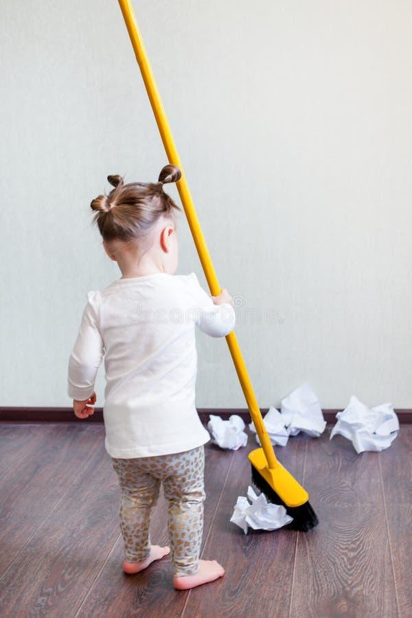 Una muchacha sostiene una escoba para 1 5 años, el concepto de limpieza de la casa, compañía de la limpieza, espacio de la limpie fotografía de archivo