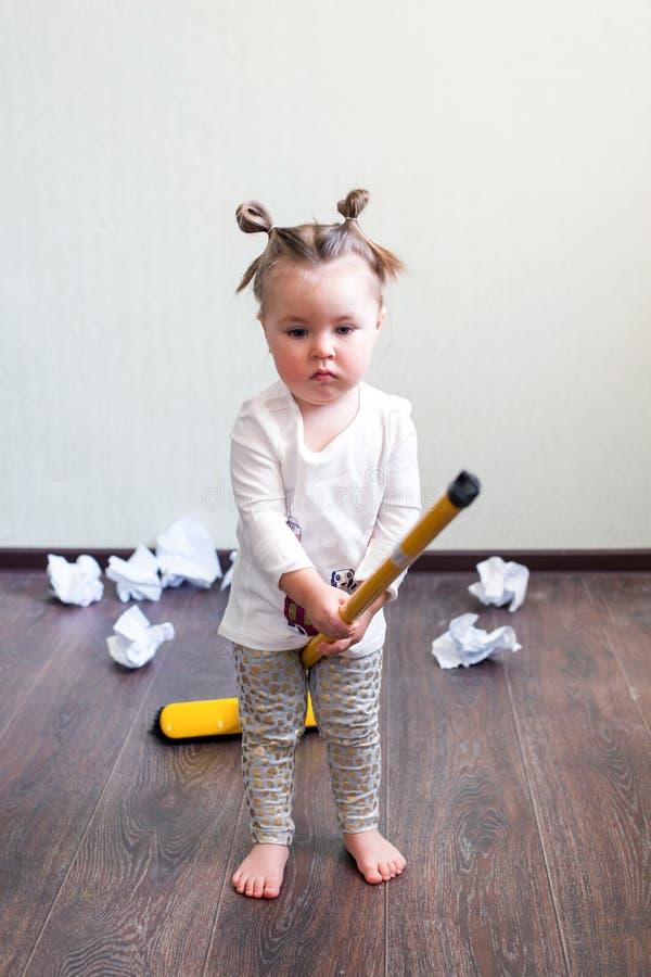 Una muchacha sostiene una escoba para 1 5 años, el concepto de limpieza de la casa, compañía de la limpieza, espacio de la limpie imagenes de archivo