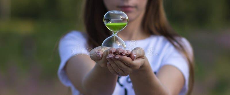 Una muchacha sostiene un reloj de arena en sus manos imágenes de archivo libres de regalías