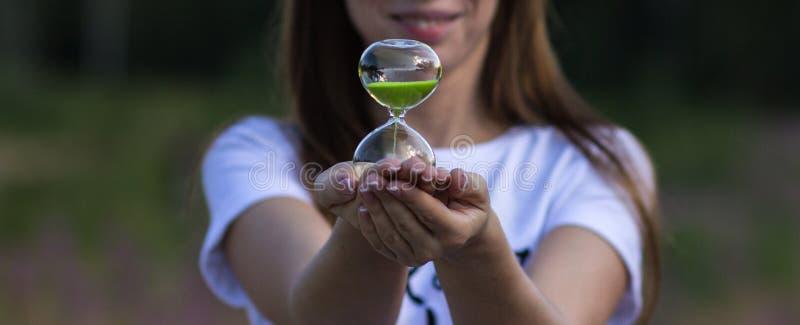 Una muchacha sostiene un reloj de arena en sus manos, primer foto de archivo libre de regalías