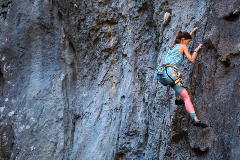 Una muchacha sube una roca fotos de archivo