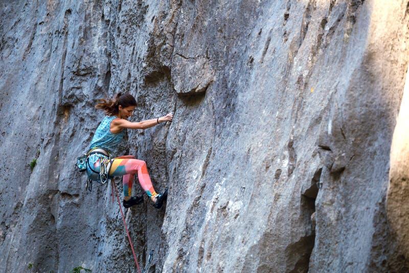 Una muchacha sube una roca imagenes de archivo