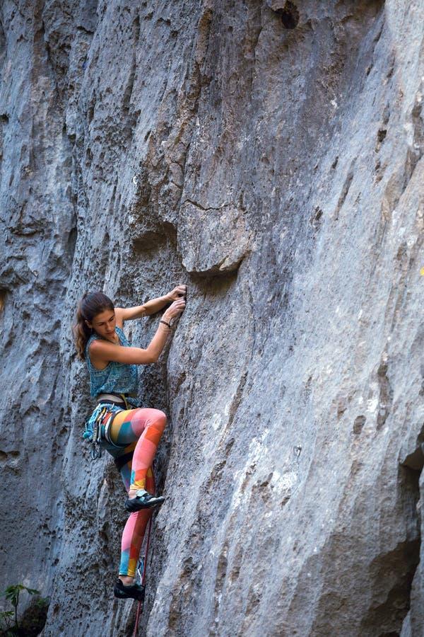 Una muchacha sube una roca fotos de archivo libres de regalías
