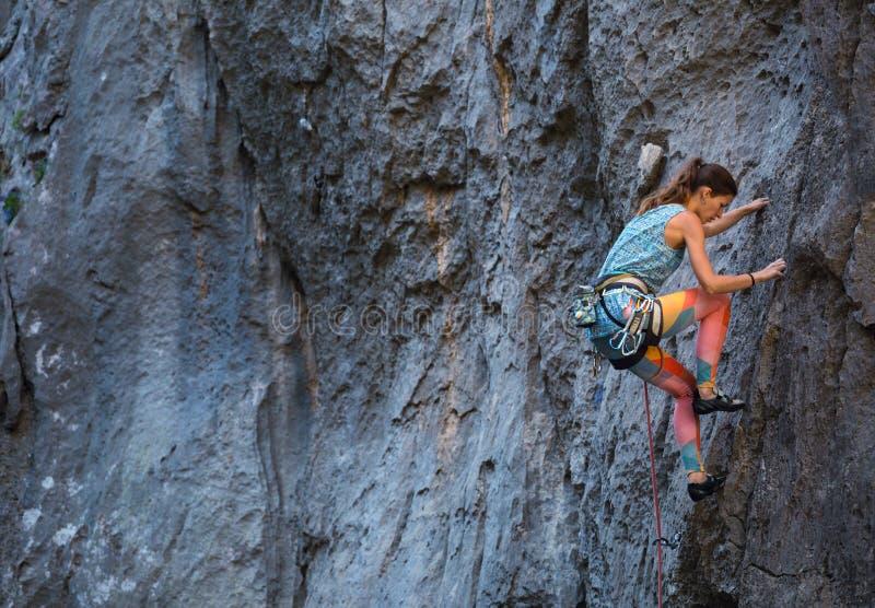 Una muchacha sube una roca fotografía de archivo
