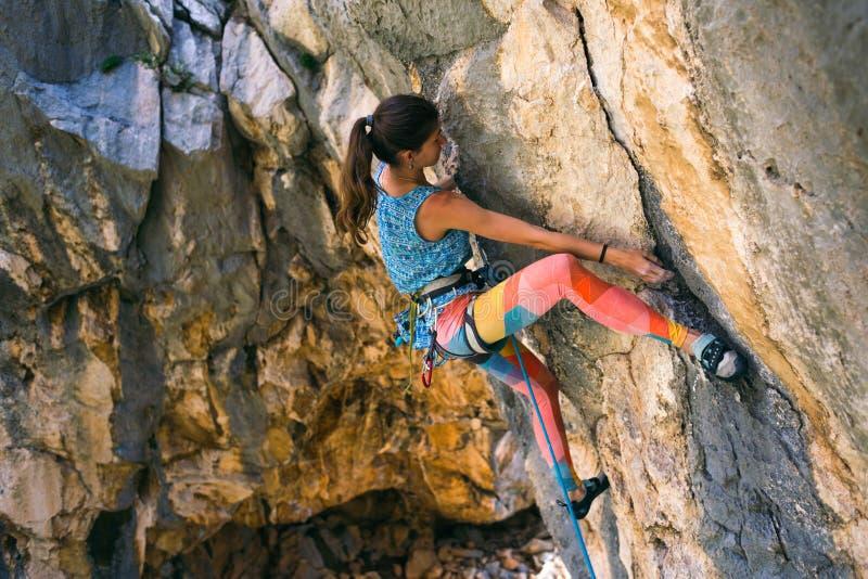 Una muchacha sube una roca foto de archivo