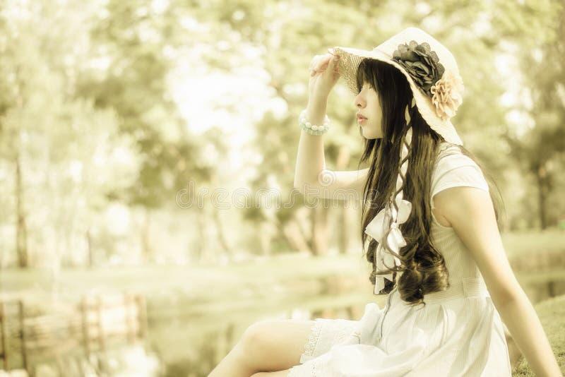 Una muchacha tailandesa asiática linda está mirando en el cielo con esperanza imagenes de archivo