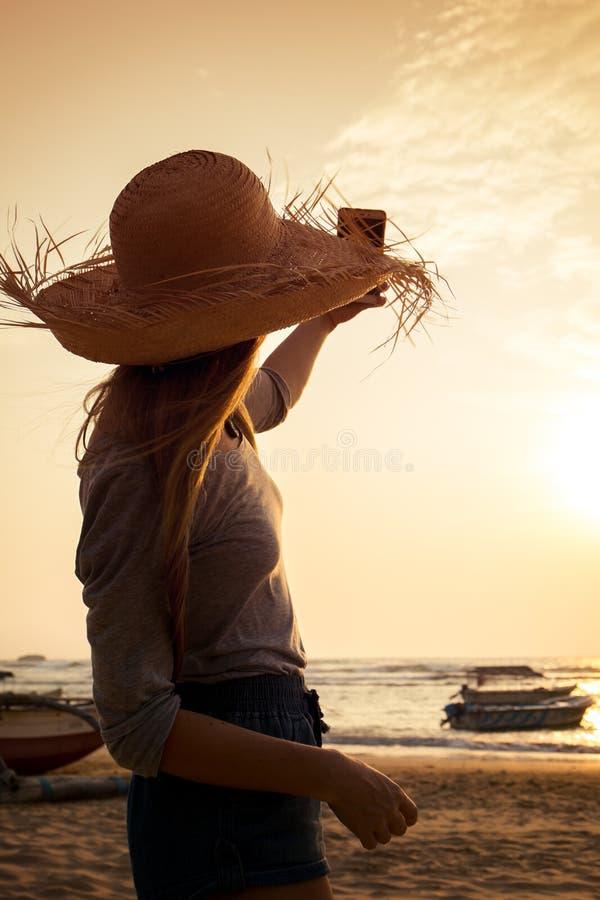 Una muchacha toma una imagen de la puesta del sol imagenes de archivo