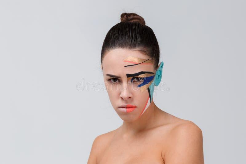 Una muchacha triste en su cara que tiene un maquillaje creativo del color fotos de archivo libres de regalías