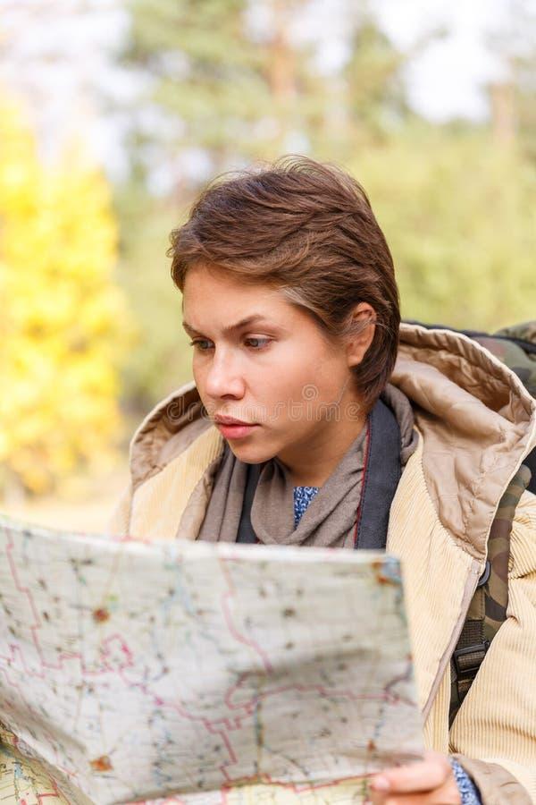 Una muchacha turística con una mochila que mira un mapa en un bosque del otoño fotografía de archivo libre de regalías